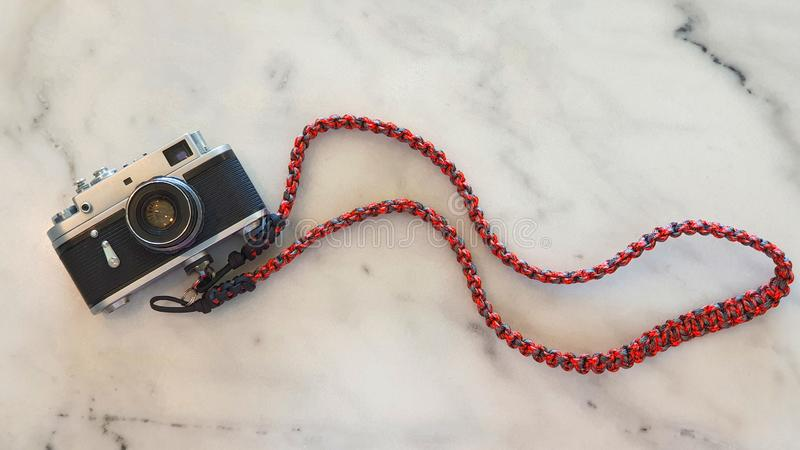 Classic Vintage Old Rangefinder Film Camera with Red Camera Strap on White Marble Table stock image