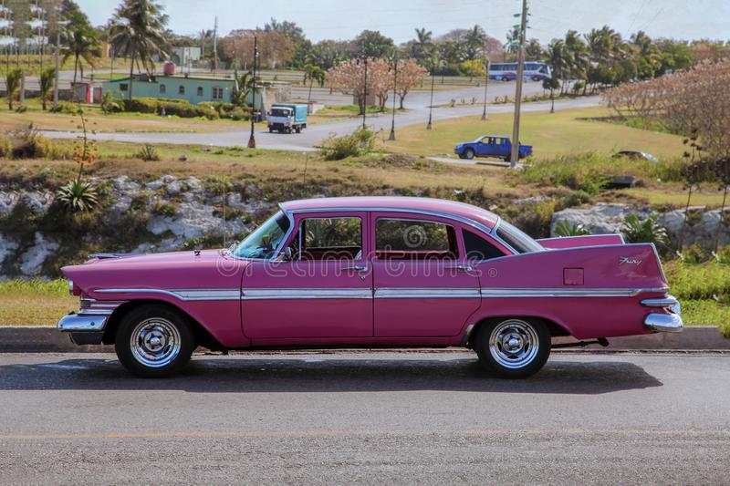 Classic vintage retro american pink car of 1959 from side proection, settled in front of a village landscape. royalty free stock photography