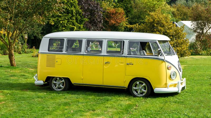 Classic vintage yellow Volkswagen Transporter camper van parked in the park, Devon, UK, August 26, 2017.  royalty free stock photo