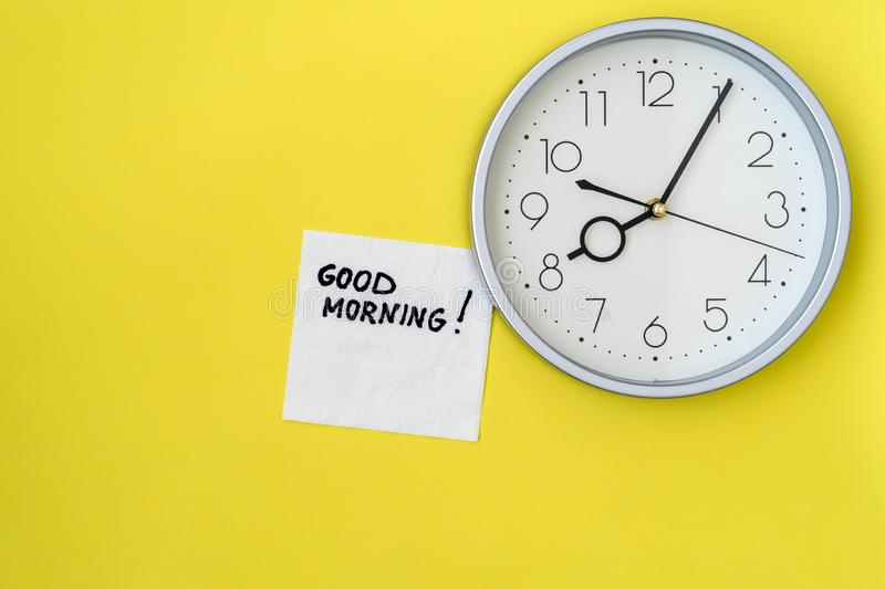Classic wall clock with GOOD MORNING note. On napkin stock image