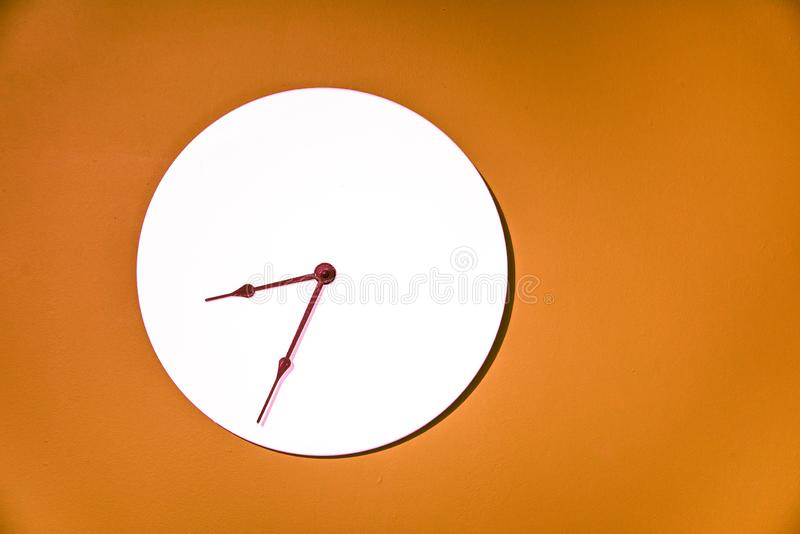 Classic wall clock hanging on an orange wall royalty free stock photo