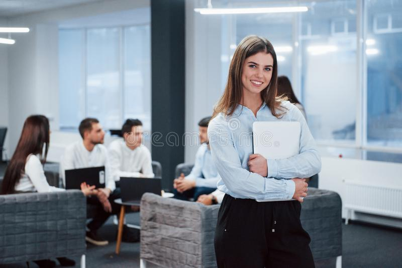 Classic wear. Portrait of young girl stands in the office with employees at background royalty free stock images