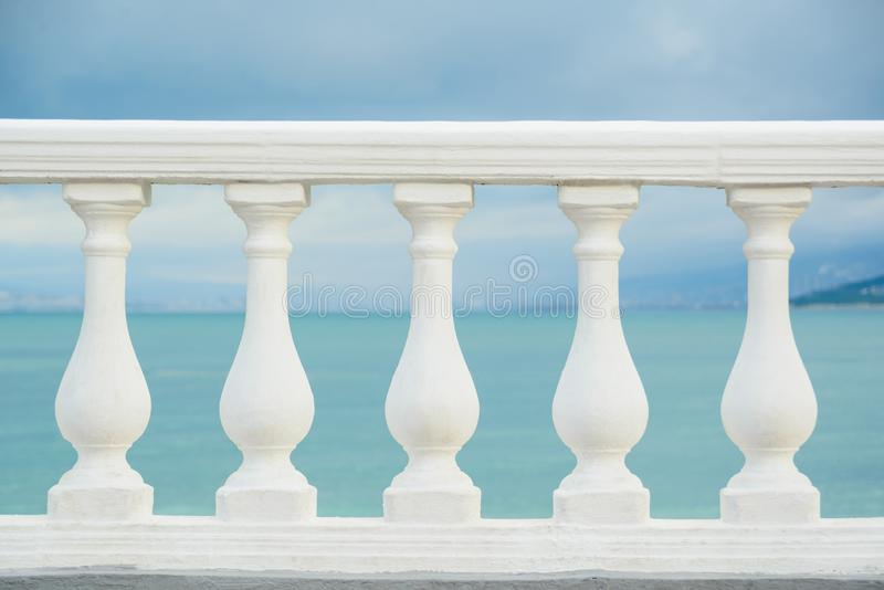 Classic white balustrade with stone columns. On blue sky and black sea water background, stock photo image stock photography