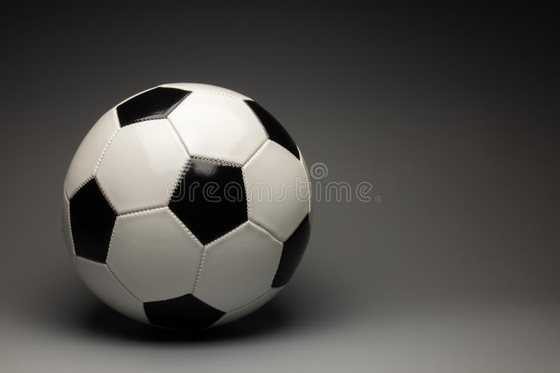 Classic white and black soccer ball on gray gradient background royalty free stock photos