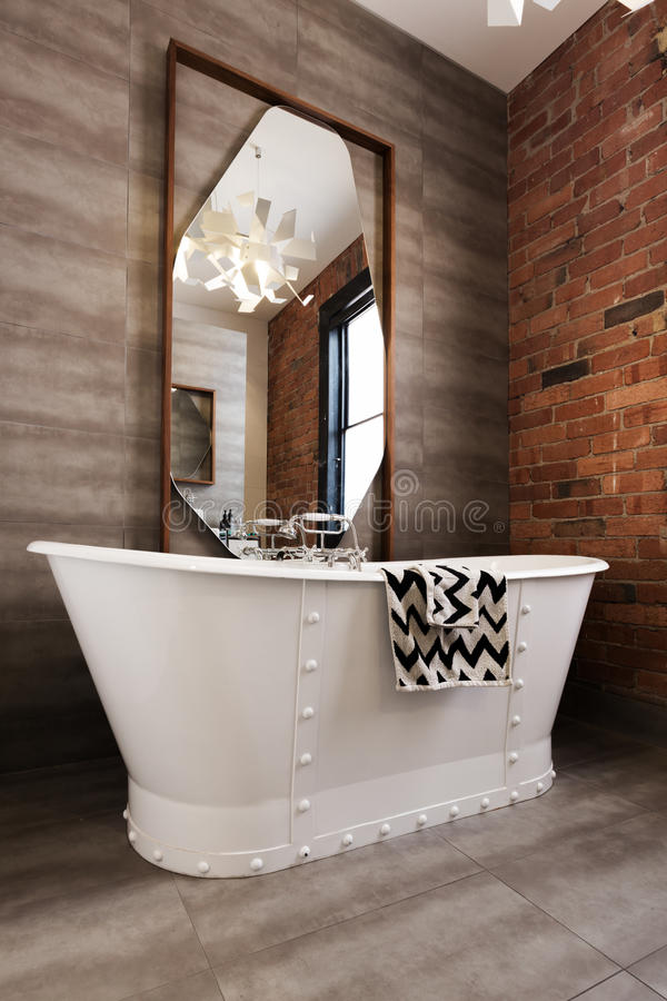 Classic white freestanding iron look bathtub in renovated bathroom stock photography