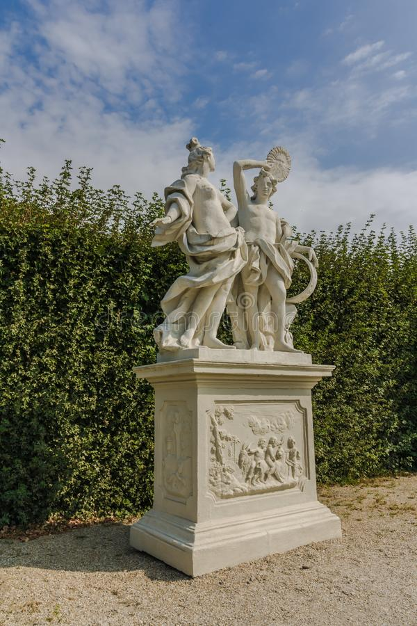 Classic white marble statue of woman with flute in green garden park. Ancient Roman or Greek woman stands on podium. the statue is. Classic white marble statue stock photos