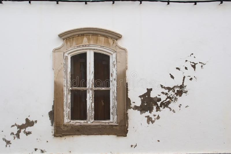 Classic window and a weathered white facade. Peeled of wooden frame of the window with a small arch, which is in a stone ornate frame. White facade of the house stock photography