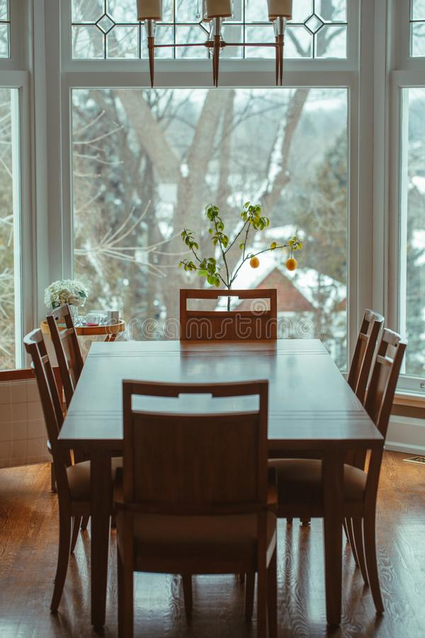 classic wooden dining table with six chairs around standing by window stock photography