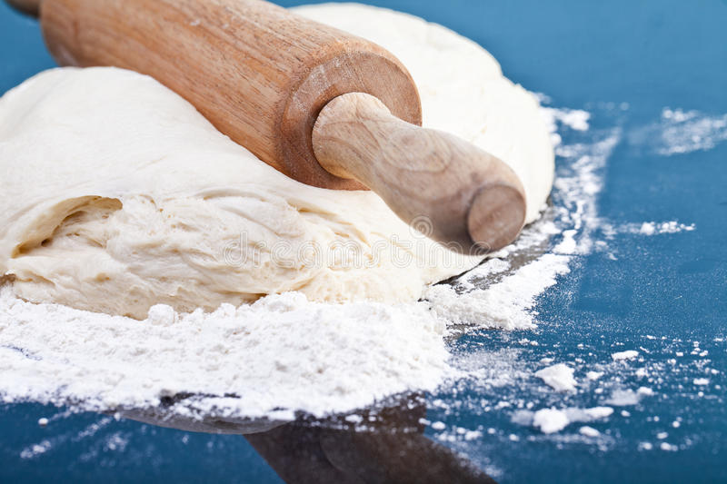 Classic wooden rolling pin with freshly prepared dough and dusting of flour on black background stock images