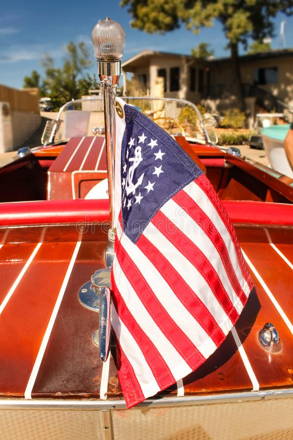 Classic wooden speed boat with nautical flag docked in front of a house on the lake - view from back with flag in focus royalty free stock photos