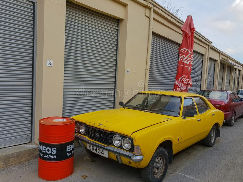 A classic yellow Ford Cortina  car is parked in an alley in the old town of Nicosia, Cyprus. Nicosia, Cyprus - 19 January, 2019: A classic yellow Ford Cortina TC royalty free stock images