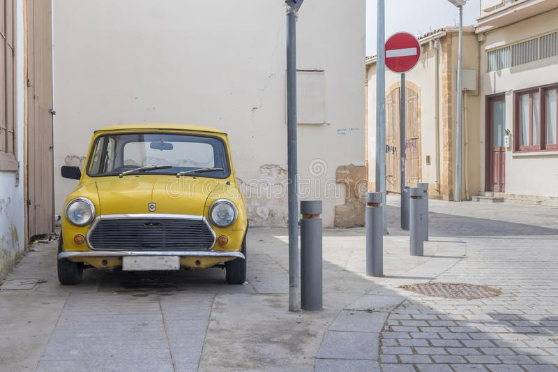 A classic yellow mini cooper parked royalty free stock image