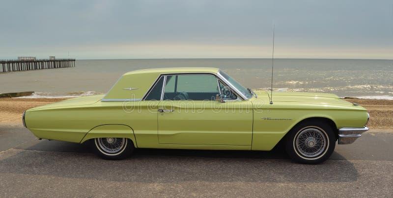 Classic Yellow Thunderbird motor car parked on seafront promenade. stock image