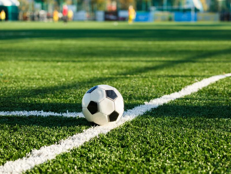 Classical black and white football ball on the green grass of the field. Soccer game, training, hobby concept. with copy space stock photos