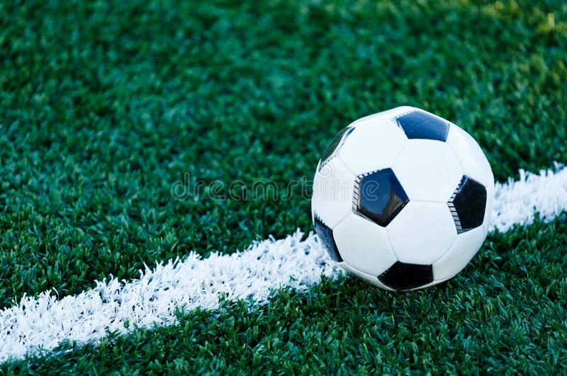Classical black and white football ball on the green grass of the field. Soccer game, training, hobby concept. with copy space stock photography