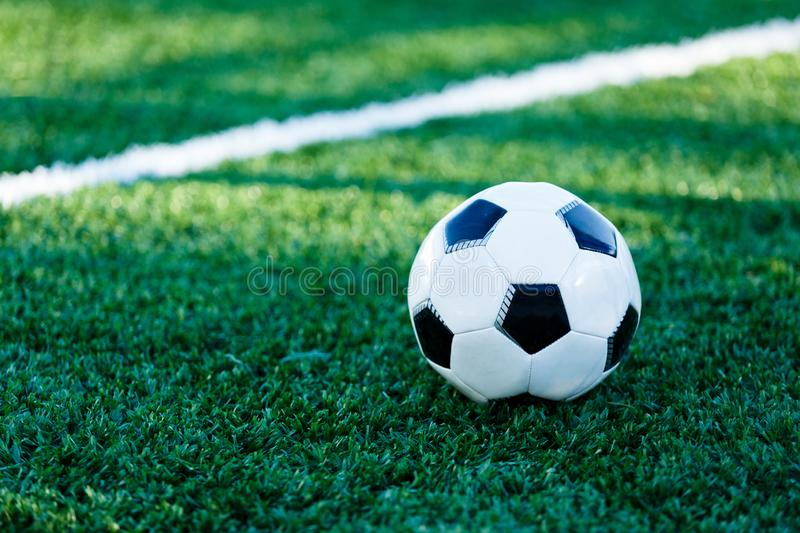 Classical black and white football ball on the green grass of the field. Soccer game, training, hobby concept. With copy space stock photo