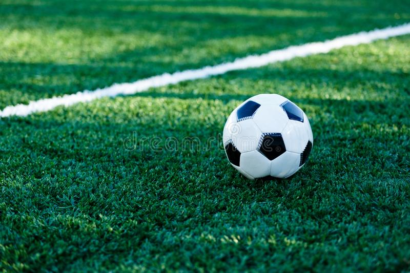 Classical black and white football ball on the green grass of the field. Soccer game, training, hobby concept. With copy space royalty free stock photos
