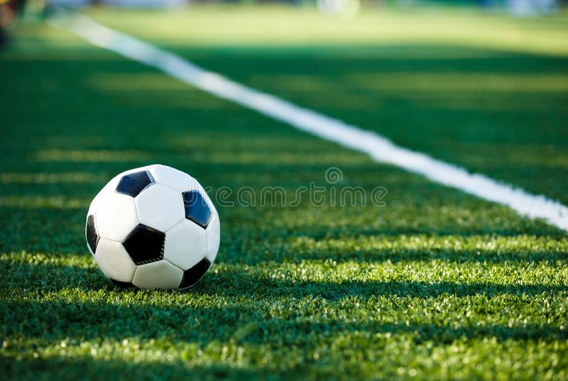 Classical black and white football ball on the green grass of the field. Soccer game, training, hobby concept. with copy space royalty free stock image