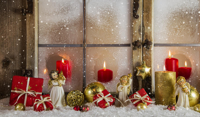 Classical christmas wooden window decoration with red candles an. Atmospheric and romantic classical christmas window decoration with red candles, snow, angels stock photos