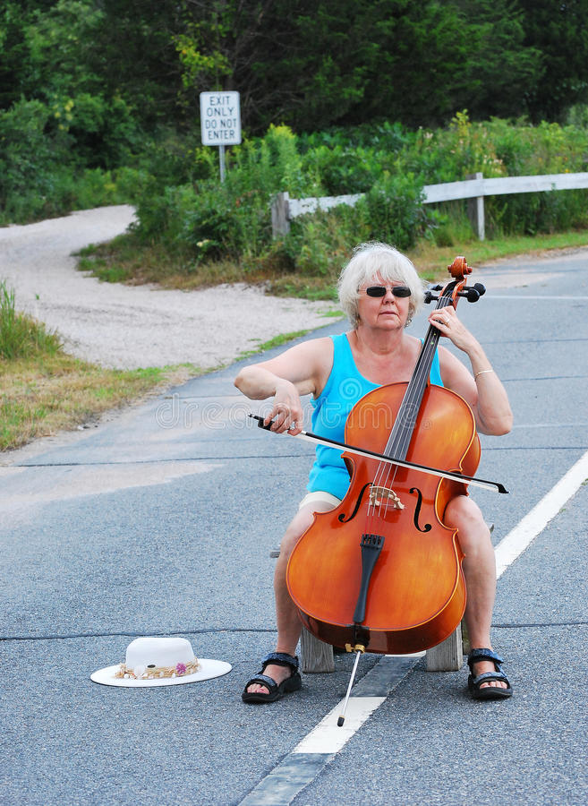 Classical concert. Female cellist performing a classical concert in the street royalty free stock photography