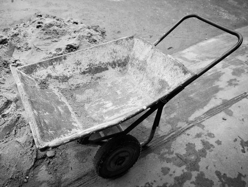 Classical concrete trolley, cement wheelbarrow. After work royalty free stock image