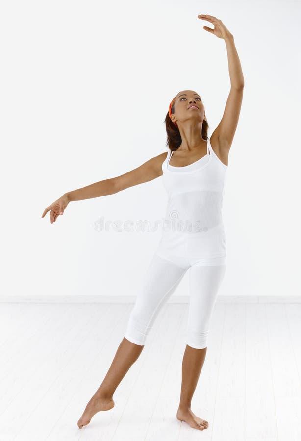 Classical dancer in posture. Pretty ethnic classical dancer in ballet posture, looking up stock images