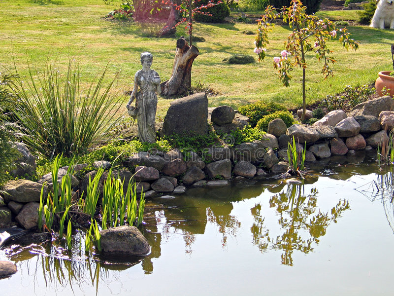 Classical garden fish pond. Classical decorated garden fish pond pool with a statue royalty free stock image
