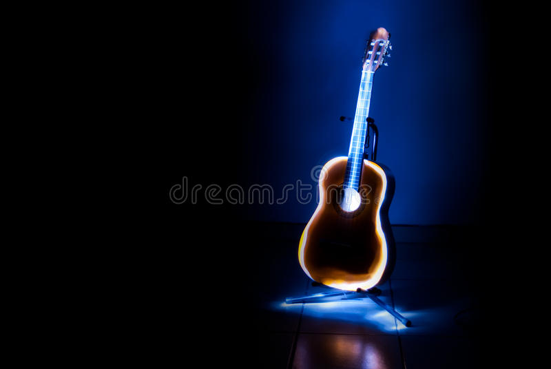 Classical guitar close up. Light painting of a classical guitar on a stand in a dark room stock photo
