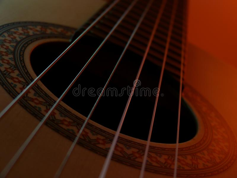 Classical guitar with golor light. Classical guitar framed in the part of the sound output with precise focus and colored background stock images