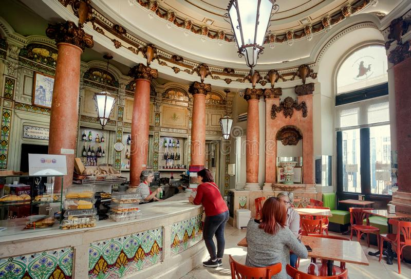 Classical interior of cafe and customers drinking coffee in vintage hall with columns royalty free stock photography
