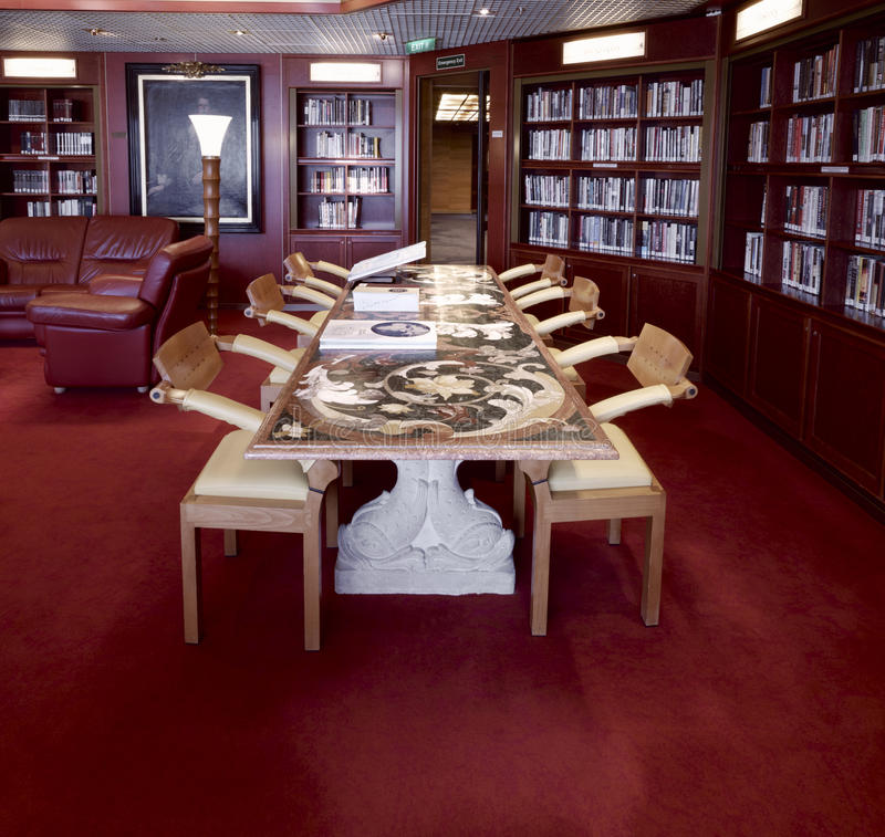 Classical library room with leather armchairs, stone table and World Atlas royalty free stock photography