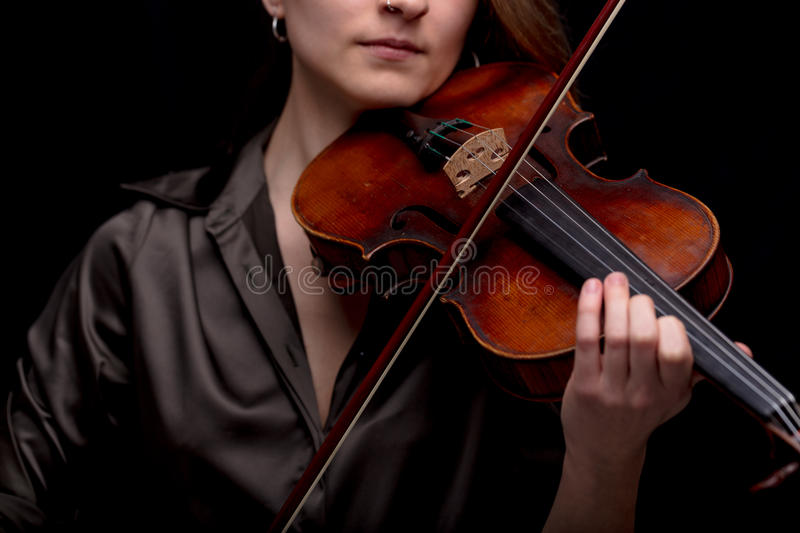 Classical music concept with unrecognizable violinist. Unrecognizable violinist woman playing her classical music instrument on a black background and enjoying royalty free stock photo
