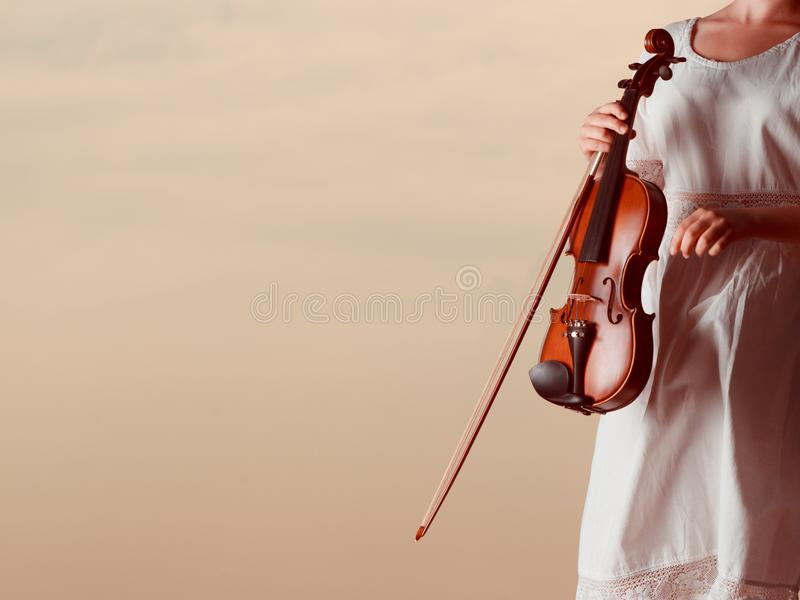 Musician violinist woman holding her violin. Classical music passion concept. Musician violinist woman holding her violin, enjoying hobby royalty free stock photos