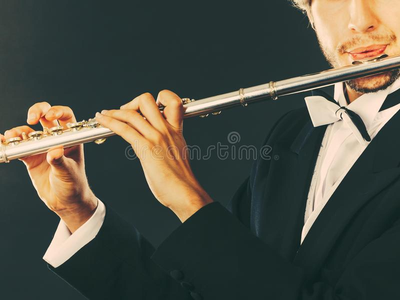 Elegantly dressed male musician playing flute. Classical music, passion and hobby concept. Elegantly dressed musician man playing on flute wearing black fedora stock images