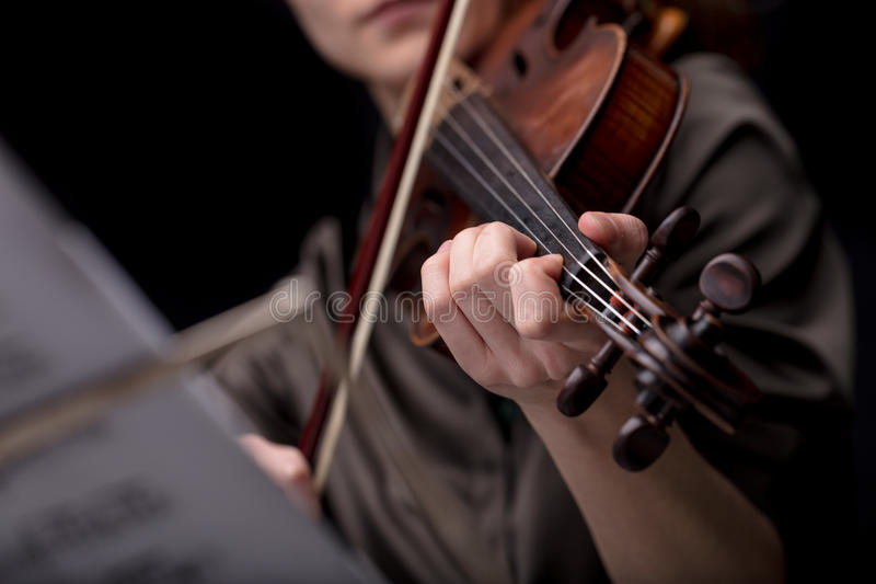 Classical music player over a dark background. Closeup of an unrecognizable musical player`s hand holding a violin while playing it. Portrait on a black room stock photo