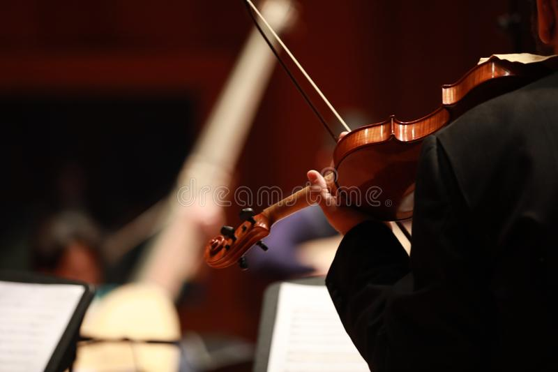 Classical music. Violinists in concert. Stringed, violinist.Closeup of musician playing the violin during a symphony stock image