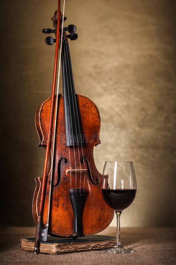 Classical old violin with red wine glass stock images