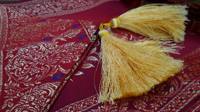 Classical pattern on colourful silk with pompom design. Pompom tail and trimming on silk material stock image