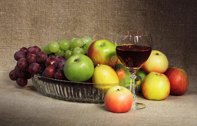 Classical still-life with fruit and glass of wine. Classical still-life with fruit and a glass of red wine against a canvas royalty free stock images