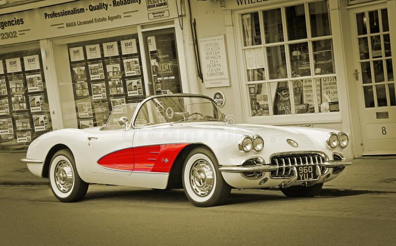 Classics roll into town. Sepia photo of a vintage chevrolet corvette c1 parked in the historic harbour town of whitstable in kent famous for its annual classic royalty free stock photos