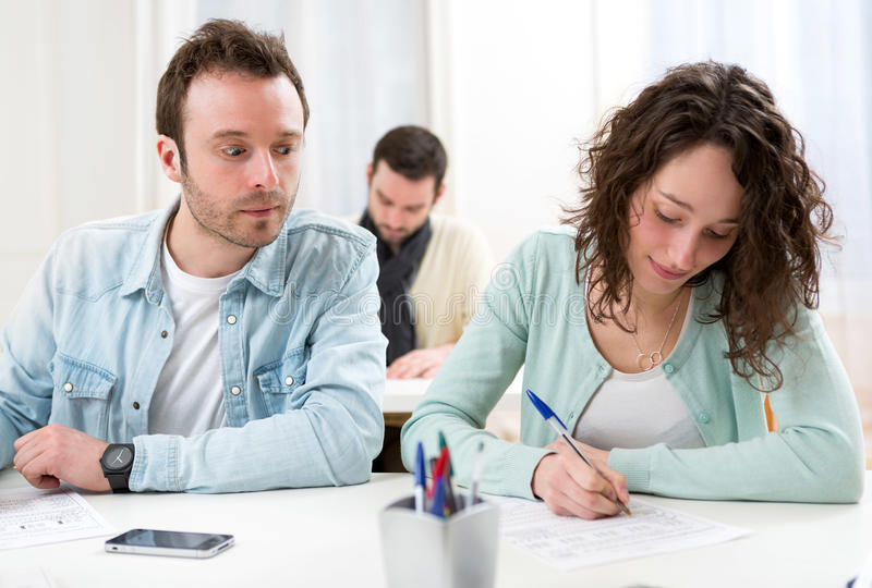 Classmate try to cheat on his neighbour stock image