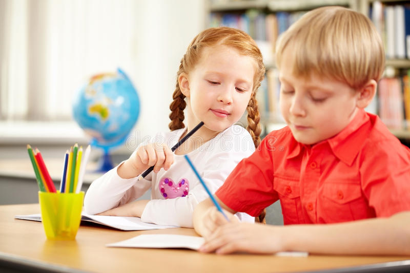 Classmates. A blond boy and a red haired girl sitting at table and drawing royalty free stock photos