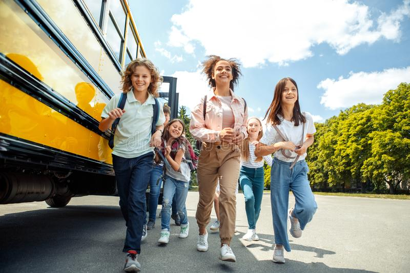 Classmates running from school bus back home looking forward smiling happy royalty free stock photography