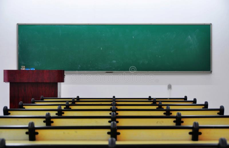 Classroom. Empty classroom with blackboard and rostrum royalty free stock images