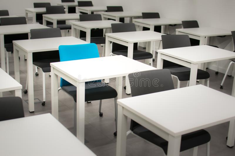 Classroom with black chairs and one blue chair. Hiring, vacant or choosing concept stock photography