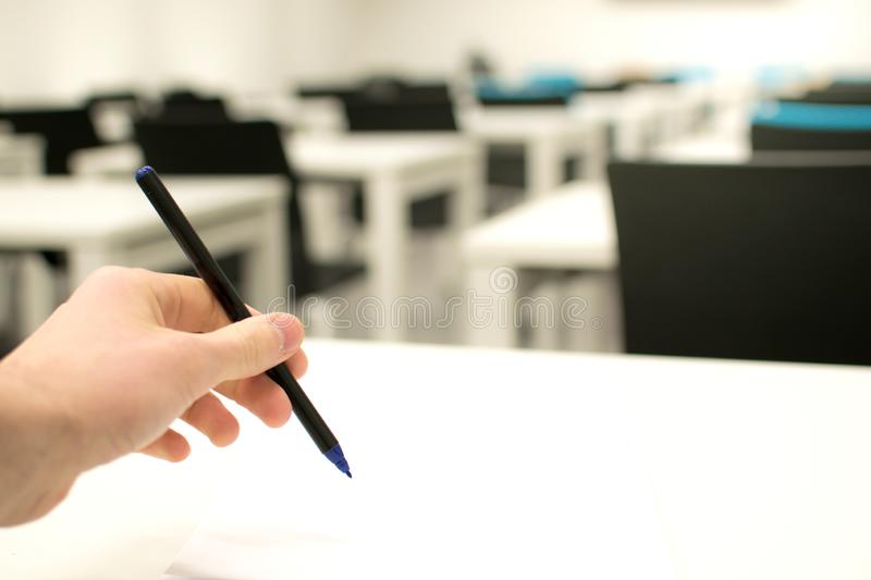 Classroom empty. High school or university student holding pen writing on paper answer sheet royalty free stock image