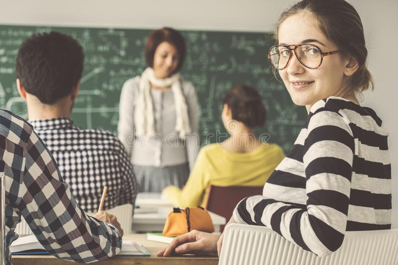 In classroom with students one of them look behind royalty free stock photography