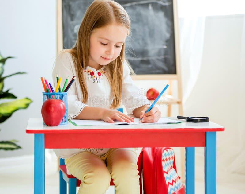 Classwork louro pequeno da escrita da menina na sala de aula da escola fotografia de stock royalty free