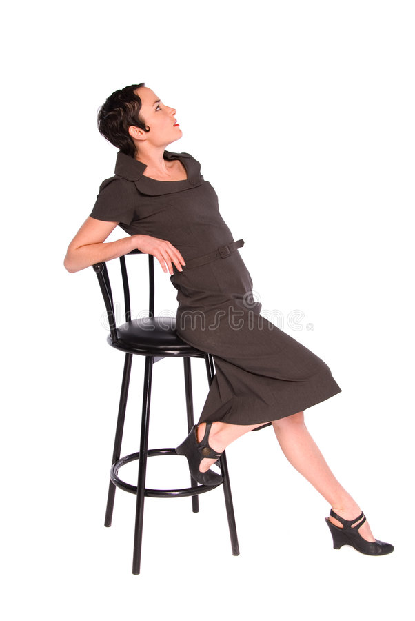 Classy 1920s style woman. Profile shot of a glamorous 1920s woman with finger curl hair style, leaning back on a stool. Isolated on white royalty free stock photography