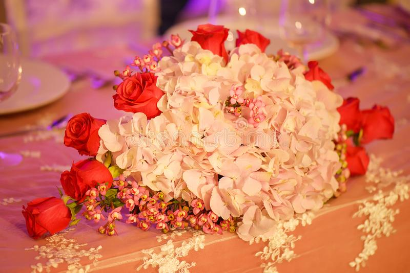Classy floral arrangement in a pastel oval bouquet featuring pink hydrangeas and red roses stock photos